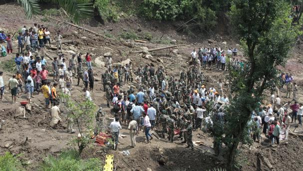 People watch army soldiers and rescue workers recover bodies of landslide victims in Urla village, Himachal Pradesh state, India (AP)