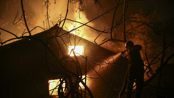 A firefighter tries to extinguish a fire at a house during a forest fire (AP)