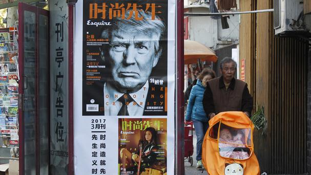 A man pushes a buggy past a magazine advertisement featuring US president Donald Trump at a news stand in Shanghai (AP)