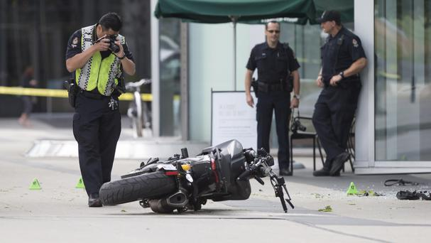 A police officer photographs a motorcycle after the stunt driver died in an on-set crash (AP)