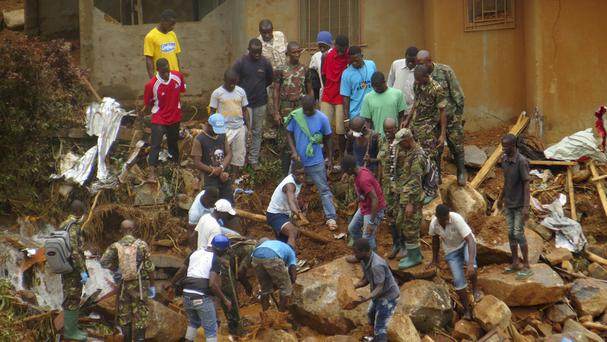 Volunteers search for bodies from the scene of heavy flooding and mudslides in Regent, just outside of Sierra Leone's capital Freetown (AP)