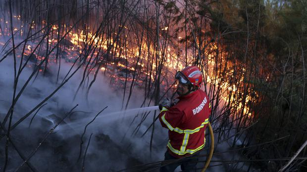 A firefighter works to put out a wildfire in central Portugal (AP/Armando Franca)
