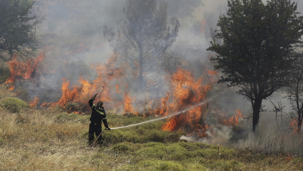 A firefighter helps tackle a blaze north of Athens (AP/Ioanna Spanou)