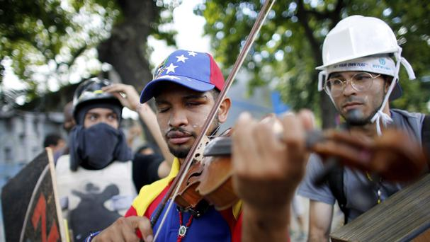 Wuilly Arteaga plays his violin during clashes with Venezuelan Bolivarian National Guards on the first day of a 48-hour general strike on July 26 (AP Photo/Ariana Cubillos, File)