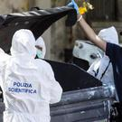 Italian police officers and forensic experts inspect a bin where body parts were discovered (AP)