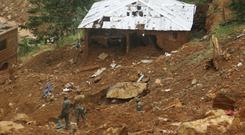 Security forces search for bodies at the scene of heavy flooding and mudslides in Regent, just outside of Sierra Leone's capital Freetown (AP)