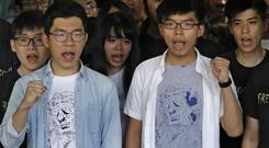 Hong Kong activist Joshua Wong, right, and Nathan Law, left, chant outside the High Court (Vincent Yu/AP)