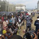 Family of victims in Regent wait to identify their bodies in Freetown (Manika Kamara/AP)