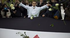 Syrian actress and activist Fadwa Suleiman, centre, throws roses on a giant Syrian flag during the White Wave campaign to protest against the violence in Syria, in Paris (Thibault Camus/AP)