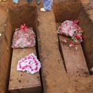 Volunteers bury coffins during a mass funeral for victims of heavy flooding and mudslides in Regent at a cemetery in Freetown, Sierra Leone on Thursday
