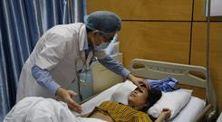 Doctor Vu Minh Dien examines dengue patient Tran Thi Xuyen at the National Hospital of Tropical Diseases in Hanoi (AP)