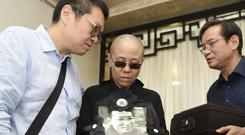 Liu Xia, wife of jailed Nobel Peace Prize winner Liu Xiaobo, holds a portrait of him during his funeral (Shenyang Municipal Information Office via AP)
