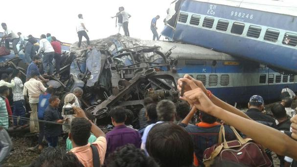 Railway police and volunteers look for survivors in the upturned coaches (AP)