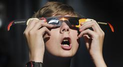 A boy tries out glasses he bought in Salt Lake City in preparation for the eclipse (Scott G Winterton/The Deseret News via AP)