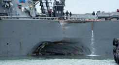 Damage to the portside is visible as the destroyer USS John S. McCain (DDG 56) steers towards Changi naval base in Singapore (Mass Communication Specialist 2nd Class Joshua Fulton/US Navy photo via AP)