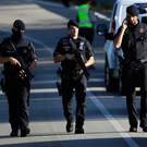Armed policemen walk on a road near Subirats, Spain. Photo: AP