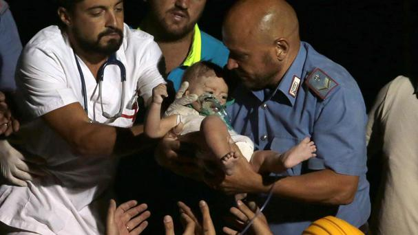 Rescuers pull seven-month-old Pasquale from the rubble of a collapsed building in Casamicciola (Ansa/AP)