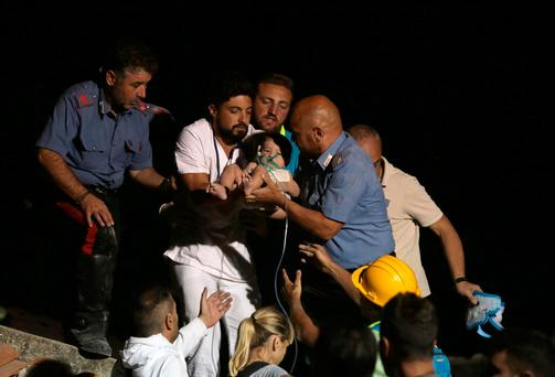 Rescuers pull seven-month-old Pasquale from the rubble of a collapsed building in Casamicciola, on the island of Ischia, near Naples, Italy. Photo: ANSA via AP