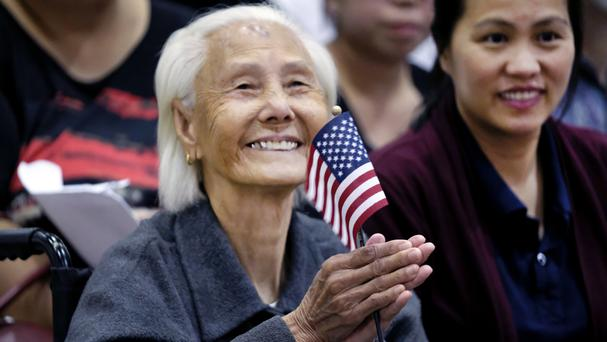 Hong Inh waves an American flag after taking the oath to become a United States citizen (AP)