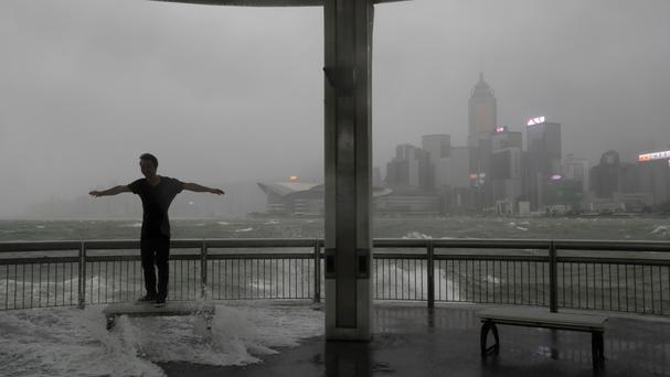 A man faces strong wind caused by Typhoon Hato on the waterfront of Victoria Harbour in Hong Kong (AP)