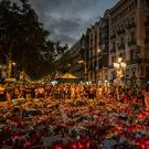 People stand next to candles and flowers after the terror attack in Barcelona, Spain. Photo: AP/Santi Palaciosas