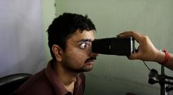 An Indian man gets his retina scanned as he enrols for an ID card in Kolkata, India. (AP/Bikas Das)