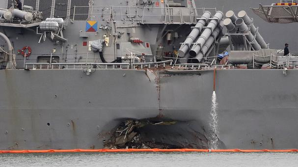 The damaged hull of the USS John S McCain is visible while docked in Singapore (AP)
