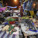Flood-affected people sleep by the national highway toll plaza at Araria district, in the eastern Indian state of Bihar (AP)