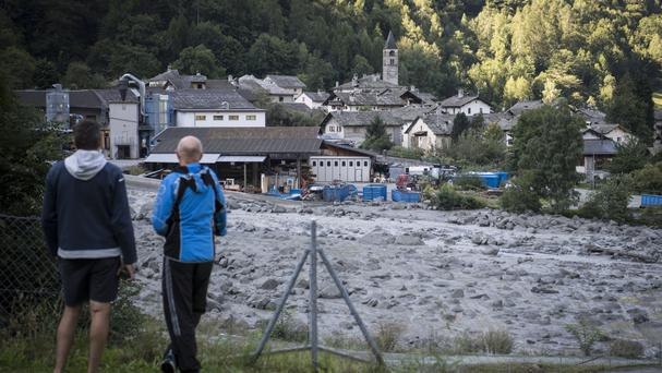 People look at the landslide that hit the village of Bondo in Graubuenden in south Switzerland (Gian Ehrenzeller/Keystone via AP)