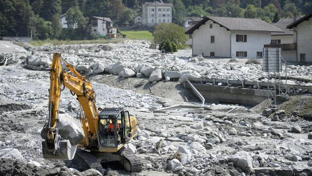 An excavator works at the site of the landslide in Bondo, Graubuenden (Keystone/AP)