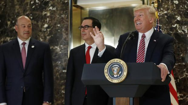 Donald Trump with Gary Cohn, left, and Steven Mnuchin, centre (AP)
