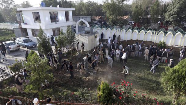 Men prepare graves for victims of the attack in Kabul (AP)