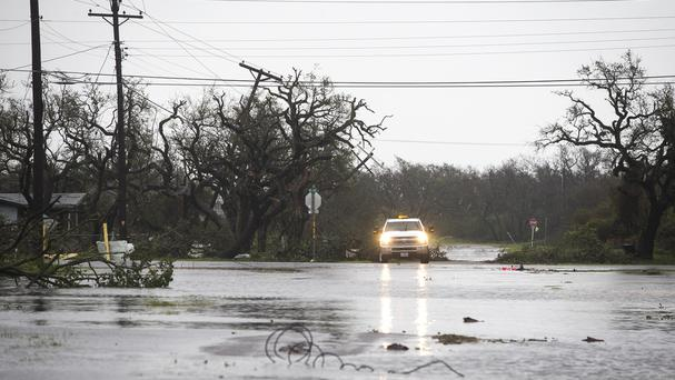 A vehicle drives through flooded roads (Nick Wagner/Austin American-Statesman via AP)
