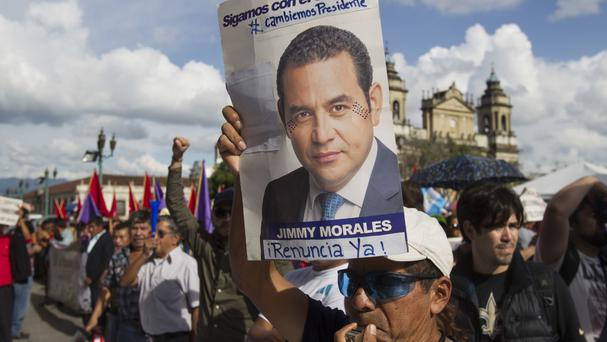 A man holds a campaign poster of Jimmy Morales during a gathering to show support for Ivan Velasquez (AP/Moises Castillo)