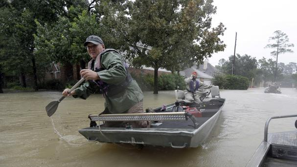 Volunteers use their boat to help evacuate residents as floodwaters from Tropical Storm Harvey rise (AP)
