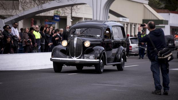 A hearse carrying the casket of All Blacks legend Colin Meads is driven through the streets of his home town of Te Kuiti