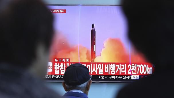 People at Seoul railway station watch a TV screen showing file footage of a North Korean missile launch (AP)