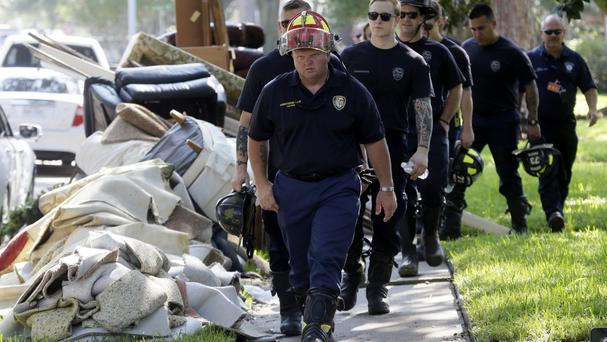 Firefighters walk around debris removed from homes during a door-to-door survey of a neighbourhood that was hit by floodwaters from in Houston (AP Photo/LM Otero)
