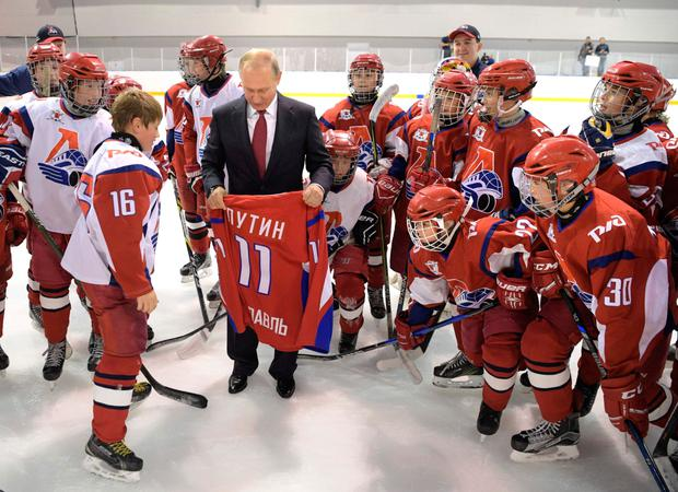 Russian President Vladimir Putin holds a jersey with his name on it as he visits the State Ice Hockey School of the Olympic Reserve in Yaroslavl, 250 km outside Moscow. Photo: Reuters