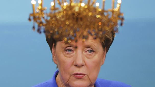 A chandelier sits in front of a screen showing German Chancellor Angela Merkel during the TV debate (Kay Nietfeld/dpa via AP)