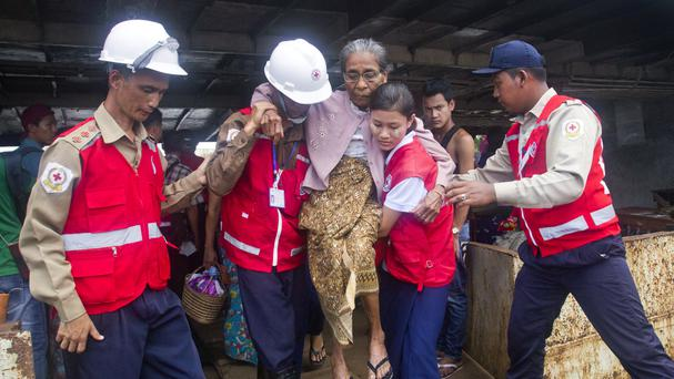 The Red Cross help an elderly woman who escaped from unrest in Maungdaw upon arrival at Sittwe jetty, Rakhine State (AP)