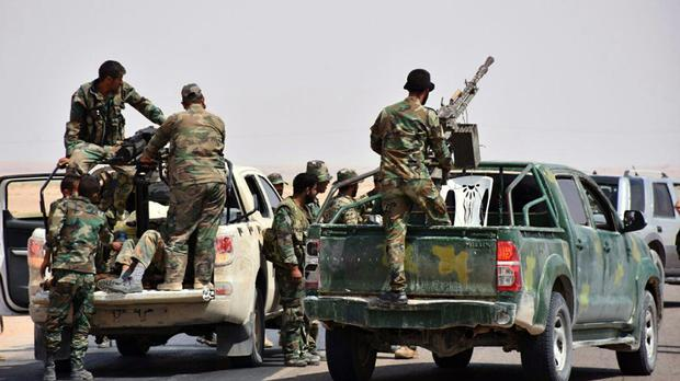 Government troops and allied gunmen in eastern Syria (Sana/AP)