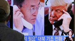 A TV shows Donald Trump and South Korean President Moon Jae-in talking on the phone Photo: AP