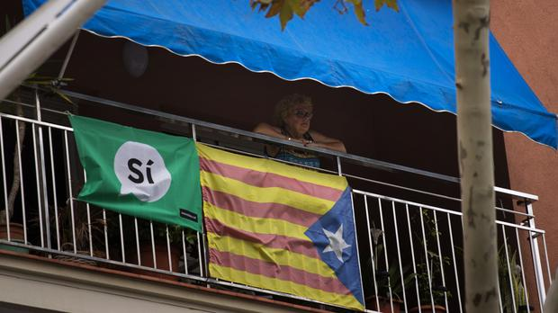 A woman looks out from her balcony decorated with an Estelada or pro-independence flag in Barcelona, Spain (AP)