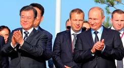 President of South Korea Moon Jae-in and Russian President Vladimir Putin applaud at an exhibition outside Vladivostok. Photo: AFP/Getty Images