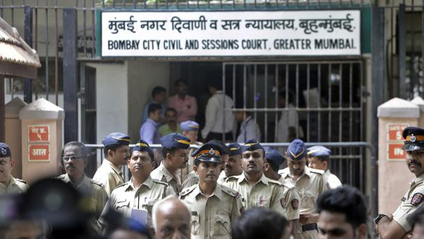 Police officials stand guard outside the court complex in Mumbai (AP)
