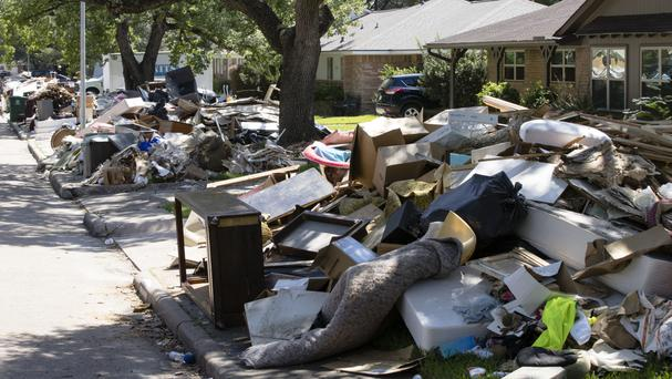 Flood-damaged debris lines a Houston street in the aftermath of Hurricane Harvey (AP)