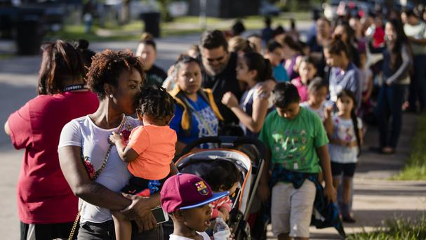 Families queue for aid at the Denver Harbour Multi-Service Centre in Houston (AP)