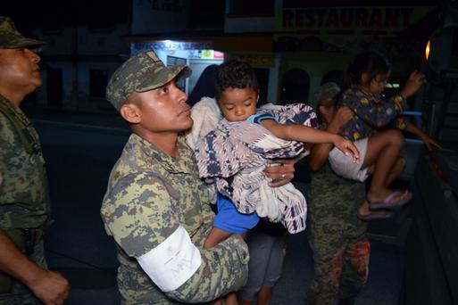 Soldiers help children to get on a truck as residents are evacuated from their coastal town after an earthquake struck off the southern coast, in Puerto Madero, Mexico. Photo: Jose Torres/Reuters