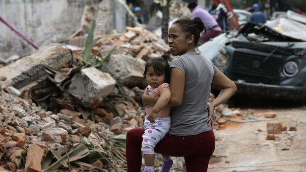 A woman holds her child in Mexico City (AP/Marco Ugarte)
